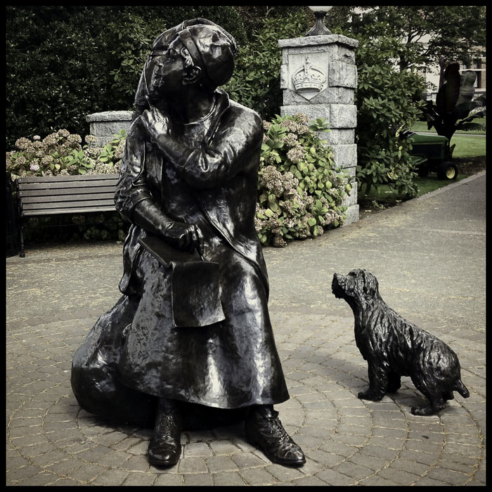 Emily Carr statue with monkey on her shoulder and dog by her side