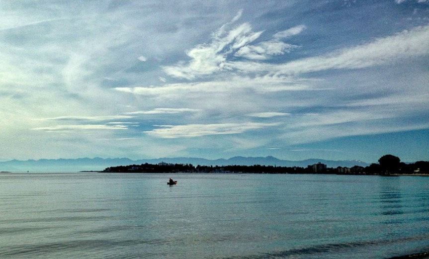 White streaking clouds and blue sky over the ocean where a lone fisherman in small boat is fishing with Olympic Mountains in far distance