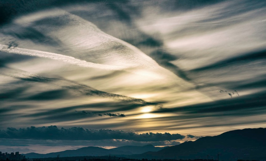 Dramatic cloud and vapour traiil pattern at sunset