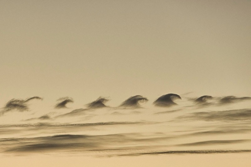 a series of clouds looking like dark stylized water waves against a pale yellow background after sunset