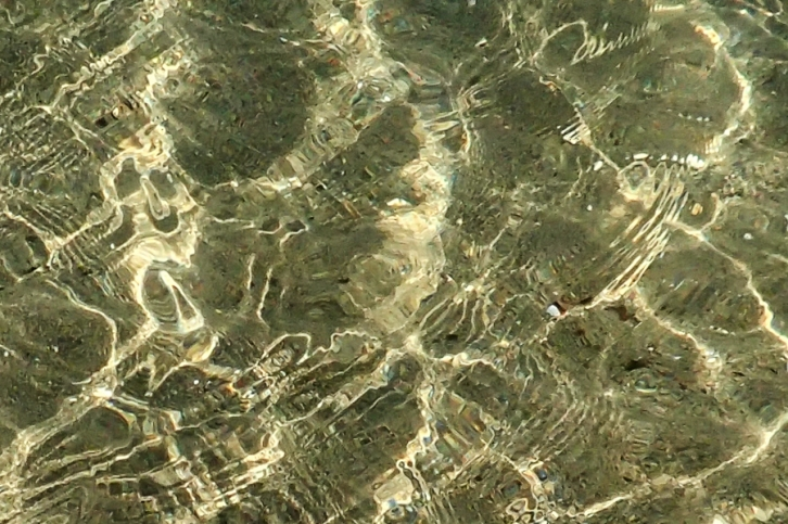 Water brightly lit over sand wiht pattern of refraction on surface