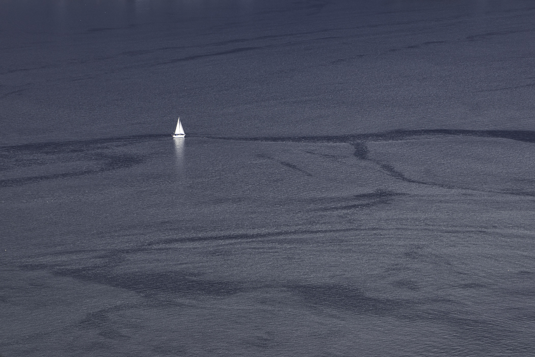 Single white-sailed boat on the ocean with dark swirl patterns, tracks of other ships