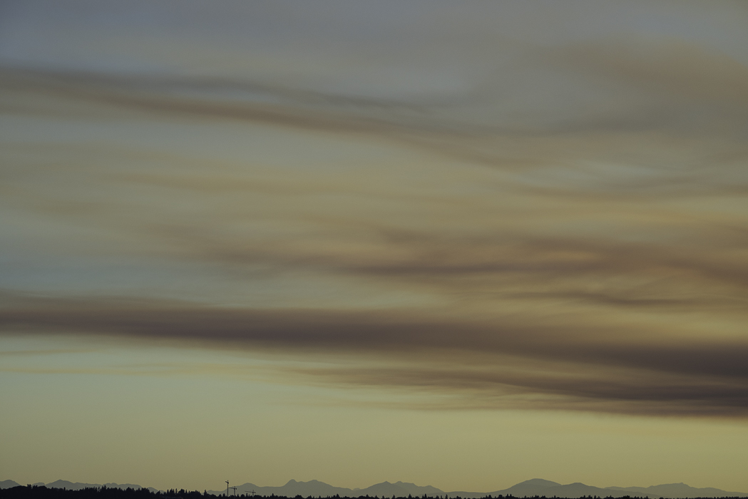 pale pink smoke plumes over yellowish sky