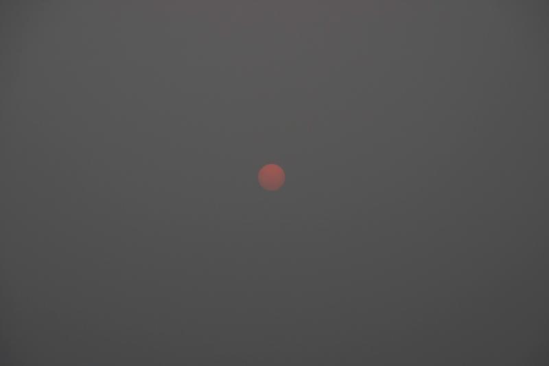 Sun as pale red ball through Smoke