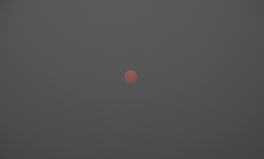Sun as pale red ball through Smoke