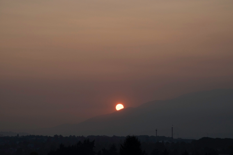 Sun setting over mountains in smoky sky